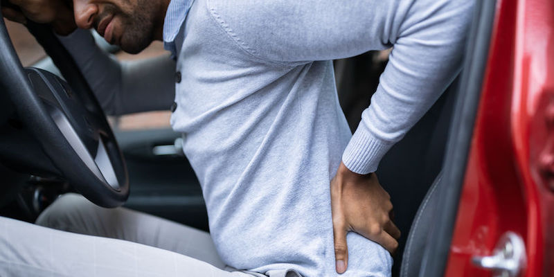 Driver Having Back Pain Sitting in a Car After Accident